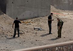 Israeli security investigates the scene of a rocket attack in Eilat, Israel, Wednesday, April 17, 2013. At least two rockets were fired at Israel's southern resort city of Eilat from Egypt's Sinai peninsula on Wednesday, the Israeli military said. (AP Photo/Ran Shauli) ISRAEL OUT