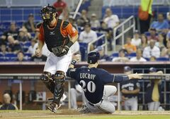 Milwaukee Brewers' Jonathan Lucroy (20) beats the throw to Miami Marlins catcher Jarrod Saltalamacchia, left, to score on a single hit by Carlos Gomez in the first inning during a baseball game on Sunday, May 25, 2014, in Miami. (AP Photo/Lynne Sladky)
