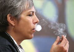 Medical-marijuana user Holly Plouffe smokes smokes at Vapes on Main.