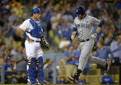 San Diego Padres' Chase Headley, right, scores on his solo home run as Los Angeles Dodgers catcher A.J. Ellis waits during the sixth inning of a baseball game, Thursday, July 10, 2014, in Los Angeles. (AP Photo/Mark J. Terrill)