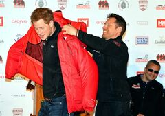 Prince Harry is presented with a red thermal coat during the launch event of the Walking With The Wounded South Pole Allied Challenge 2013 at the Mandarin Oriental Hotel, London, Friday April 19, 2013. Prince Harry will take part in a race to the South Pole with a team of wounded British servicemen and women, he announced today. The 28-year-old will take on teams from the United States and the Commonwealth in the 208-mile (335km) Walking With The Wounded South Pole Allied Challenge in November and December this year.(AP Photo, PA, John Stillwell) UNITED KINGDOM OUT NO ARCHIVE NO SALES
