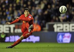 Liverpool's Luis Saurez scores from a free kick against Wigan Athletic during the English Premier League soccer match at the DW Stadium, Wigan, England, Saturday March 2, 2013. Liverpool won the match 0-4. (AP Photo/PA, Clint Hughes) UNITED KINGDOM OUT NO SALES NO ARCHIVE