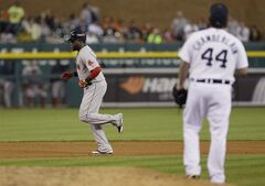 Boston Red Sox designated hitter David Ortiz, left, rounds the bases as Detroit Tigers relief pitcher Joba Chamberlain looks on after Ortiz's three-run home run during the ninth inning in a baseball game in Detroit, Sunday, June 8, 2014. (AP Photo/Carlos Osorio)