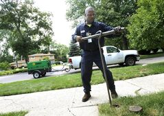 FILE-- In this July 8, 2014 file photo, Chester Clemons, a water shut-off technician for the city of Detroit, shuts off the water at a home in the Palmer Woods neighborhood of Detroit. State-appointed emergency manager Kevyn Orr issued an order placing control of Detroit's water department in the hands of Mayor Mike Duggan. The move was announced Tuesday, July 29, 2014 and comes as the massive water system in the bankrupt city has received national and international criticism for shutting off service to thousands of customers who are 60 days or more behind on their bills. (AP Photo/The Detroit News, Elizabeth Conley)