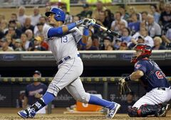 Kansas City Royals' Salvador Perez (13) follows through on a two-run single to center field off Minnesota Twins starting pitcher Trevor May during the fifth inning of a baseball game in Minneapolis, Monday, Aug. 18, 2014. Watching the flight of the ball is Minnesota Twins catcher Eric Fryer. (AP Photo/Ann Heisenfelt)