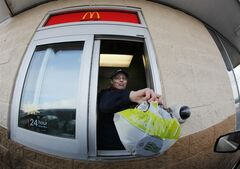 FILE - In this Jan. 26, 2009 file photo, McDonald's employee Cortney Sobowiec hands a patron a salad at the drive up window at McDonalds in Williamsville, N.Y. McDonald's understands its reputation for serving cheap, greasy fare is a growing liability and is trying to change in a variety of ways. (AP Photo/David Duprey, file)