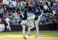 San Diego Padres' Alexi Amarista, left, and Cameron Maybin celebrate at the end of the ninth inning of a baseball game against the New York Mets, Saturday, June 14, 2014, in New York. San Diego won 5-0. (AP Photo/Jason DeCrow)