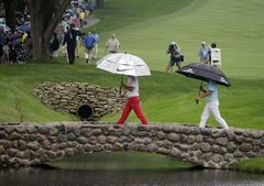 Rory McIlroy, from Northern Ireland, center, and Rickie Fowler cross the bridge on the 16th hole as play in the third round of the Bridgestone Invitational golf tournament is delayed by lightening on Saturday, Aug. 2, 2014, at Firestone Country Club in Akron, Ohio. (AP Photo/Mark Duncan)