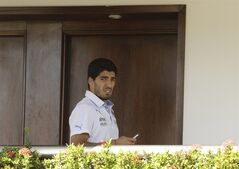 Uruguay's Luis Suarez uses his cell phone at a hotel in Natal, Brazil, Wednesday, June 25, 2014. Suarez bit Italian player Giorgio Chiellini during Uruguay's game with Italy on Tuesday, which could lead to Suarez being kicked out of the World Cup. (AP Photo/Hassan Ammar)