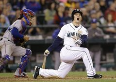 Seattle Mariners' Kyle Seager, right, lets out a yell after swinging and missing to strike out and end the sixth inning of a baseball game as Texas Rangers catcher Robinson Chirinos heads back to the dugout Saturday, June 14, 2014, in Seattle. (AP Photo/Elaine Thompson)
