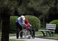 In this Thursday, May 23, 2013 photo, an elderly man helps his wife on a wheelchair at a park in Beijing. New wording in the law requiring people to visit or keep in touch with their elderly parents or risk being sued came into force Monday, as China faces increasing difficulty in caring for its aging population. (AP Photo/Andy Wong)