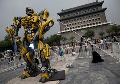 A child stands on a barricade fence looks at a replica model of Transformers character Bumblebee on display in front of Qianmen Gate, as part of a promotion of the movie