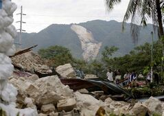 With a landslide in background residents gather near the rubble of Maribojoc Church at Maribojoc township, Bohol province in central Philippines Thursday Oct.17, 2013. A 7.2-magnitude quake hit Bohol and Cebu provinces, Tuesday damaging buildings homes, churches and infrastructure and causing multiple deaths across the central region. (AP Photo/Bullit Marquez)