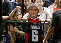 A fan of NBA star LeBron James holds a picture of James during a promotional event at a shopping district in Hong Kong as part of his China tour Wednesday, July 23, 2014. Earlier this month, James left the Miami Heat after four seasons and four trips to the NBA Finals and re-signed with the Cavaliers, where his career began. (AP Photo/Kin Cheung)
