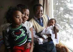 From left, Remedia Ayingono holds daughter Joaquina Nsang-Ntutumu, 2, with husband Alberto Ntutumu Asue and baby daughter Candida Asue- Ntutumu in their home in Winnipeg.  The family of seven has immigrated to Canada from Equatorial New Guinea as refugees.