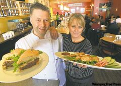 Dave Schultz shows off a pulled bison sandwich and Trish Cantafio holds chicken satay at River Heights cafe Saucers.