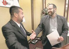 Rabbi Or Rose (right) greets Imam Abdullah Antepli at a unity seminar Sunday.