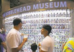 Fans look at dolls in the Bobblehead Museum at Marlins Park during a spring training baseball game between the Miami Marlins and the New York Yankees in Miami, Monday, April 2, 2012. (AP Photo/Wilfredo Lee)