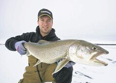 Darren Bohonis releases a lake trout.
