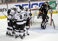 Los Angeles Kings center Anze Kopitar (11), of Slovenia, and defenseman Drew Doughty (8) celebrate defenseman Alec Martinez (27) scoring against Anaheim Ducks goalie Jonas Hiller (1), of Switzerland, in the first period in Game 1 of an NHL hockey second-round Stanley Cup playoff series in Anaheim, Calif., Saturday, May 3, 2014. (AP Photo/Alex Gallardo)