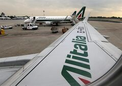 FILE- In this Wednesday, May 7, 2014, file photo, Alitalia planes wait on the tarmac prior to take off from the Linate airport, in Milan, Italy. Fast-growing Gulf carrier Etihad Airways says it and Alitalia have reached a deal in principle for the United Arab Emirates-based airline to buy a 49 percent stake in the struggling Italian airline. (AP Photo/Luca Bruno, File)