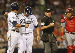 San Diego Padres first base coach Jose Valentin restrains Everth Cabrera as umpire David Rackley stands between the Padres and St. Louis Cardinals catcher Tony Cruz after the Cardinals hit Cabrera with a pitch during the Padres' eight run seventh inning in a baseball game Wednesday, July 30, 2014, in San Diego. (AP Photo/Lenny Ignelzi)