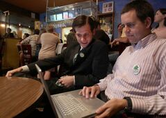 Mike Moreau, right, looks over election results with Green Party leader James Beddome at the Bella Vista restaurant Tuesday night.