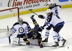 Sabres' Tyler Ennis battles for the puck with Jets' Ron Hainsey and Mark Stuart in front of Winnipeg goaltender Ondrej Pavelec in Buffalo on Monday night.