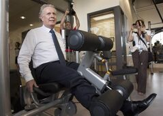 Quebec Liberal Leader Jean Charest tries out gym equipment reserved for the working staff while visiting a cookie factory Thursday, August 9, 2012 in Saint-Augustin-de-Desmaures Que. Quebecers are going to the polls on Sept. 4. THE CANADIAN PRESS/Jacques Boissinot