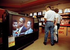 FILE - In this June 20, 1994 file photo, mall shoppers in Tampa, Fla., watch banks of televisions in an electronics store as the arraignment of O.J. Simpson is televised from Los Angeles. The O.J. Simpson trial was labeled the