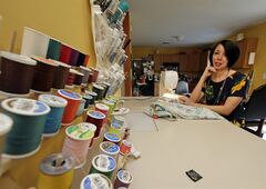 """In this July 16, 2014 photo, Jillian Owens poses with her sewing materials at her home in Columbia, S.C. Since 2010, the 32-year-old Columbia resident has been delving into thrift store racks around the area, taking what some may see as """"ugly"""" pieces and whipping them into hip, trendy fashions. (AP Photo/Chuck Burton)"""