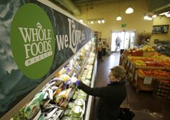 In this March 27, 2014 photo, a woman shops at the Whole Foods Market in Woodmere Village, Ohio. Whole Foods reports quarterly financial results on Wednesday, July 30, 2014. (AP Photo/Tony Dejak)