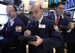 FILE- In this Thursday, Dec. 6, 2012, file photo, Trader Fred DeMarco, center works on the floor of the New York Stock Exchange. World stock markets swung higher Friday Dec. 14, 2012 after a survey showed an improvement in China's manufacturing, offsetting gloom from a sharp drop in Japanese business confidence. (AP Photo/Richard Drew, File)