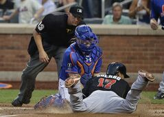 New York Mets catcher Travis d'Arnaud tags out Miami Marlins second baseman Donovan Solano (17) at the plate after he tried to score from first base on a double by Casey McGehee in the fourth inning of a baseball game, Friday, July 11, 2014, in New York. (AP Photo/Julie Jacobson)