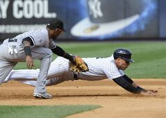 Chicago White Sox shortstop Alexei Ramirez, left, tags out New York Yankees' Martin Prado on a fielder's choice during the fourth inning of a baseball game Saturday, Aug. 23, 2014, at Yankee Stadium in New York. (AP Photo/Bill Kostroun)