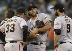San Francisco Giants' Madison Bumgarner, center, is visited by pitching coach Dave Righetti (33) and Brandon Belt (9) in the third inning of a baseball game against the Oakland Athletics Tuesday, July 8, 2014, in Oakland, Calif. (AP Photo/Ben Margot)