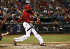 Texas Rangers' Alex Rios swings for a two-run single against the Los Angeles Angels during the seventh inning of a baseball game, Saturday, Aug. 16, 2014, in Arlington, Texas. The Angels won 5-4. (AP Photo/Jim Cowsert)