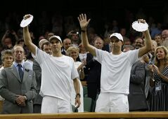 Bob Bryan, right, and Mike Bryan of the U.S hold up their runner up trophies after being defeated in the men's doubles final after Vasek Pospisil of Canada and Jack Sock of the U.S at the All England Lawn Tennis Championships in Wimbledon, London, Saturday July 5, 2014. (AP Photo/Sang Tan)