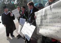 Protesters outside the University of Winnipeg are approached by graduating student David Baxter, who opposed their demonstra­tion.