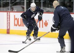 Rookie hopeful Mark Scheifele  gets ready to put a deke on assistant coach Charlie Huddy during Thursday's practice.