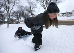 Kate Persson, 10, pulls her brother, Thomas, 6, in a sled in fresh snow in Transcona. While the snow had young folk out playing across Winnipeg, city crews will be out working to clear it off roads, with residential parking bans going into effect in some areas on Monday morning.