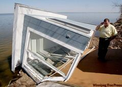 John McNicholl examines his sunroom, damaged by last fall's weather bomb and finished off by ice earlier this year.