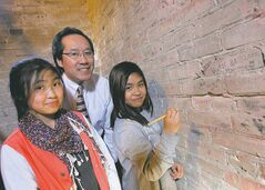 Principal Lionel Pang, Nicole Valencia (left) and Allayssa Palomeno, both 11, show bell-tower bricks with former students' names.