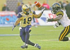The Blue Bombers' Chris Garrett (left) bobbles a pass as the Tiger-Cats' Renauld Willams pursues during first-half action Wednesday.