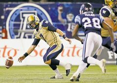 The ball slips from quarterback Alex Brink's hands as Argos' Brandon Isaac comes charging in during the second half Wednesday night at Rogers Centre.