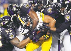 Pittsburgh Steelers running back Isaac Redman (33) is stopped by Baltimore Ravens outside linebacker Terrell Suggs (55), inside linebacker Jameel McClain (53), outside linebacker Courtney Upshaw (91) and cornerback Corey Graham (24) defense during the second half of an NFL football game in Baltimore, Sunday, Dec. 2, 2012. (AP Photo/Nick Wass)