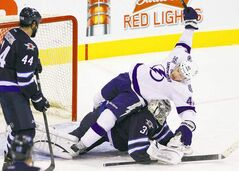 The Tampa Bay Lightning's Dana Tyrell takes a tumble over Jets goaltender Ondrej Pavelec as Zach Bogosian looks on during the first period Sunday.