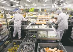 Diet aides (far left) quickly add servings customized to individual patients as the trays move along a conveyor belt.