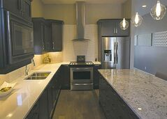 Kitchen finishes include quartz countertops, smoke maple cabinets and an off-white tile backsplash.