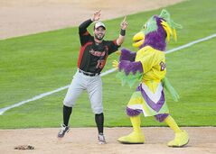 Grand Prairie Air Hogs' Adel Nieves dances with a mascot during a break in play.